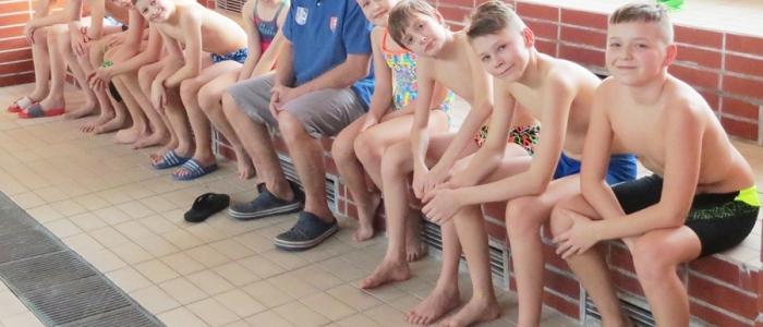 Družina mladších plavcov humenského klubu Chemes s trénerom Jánom Pencákom.